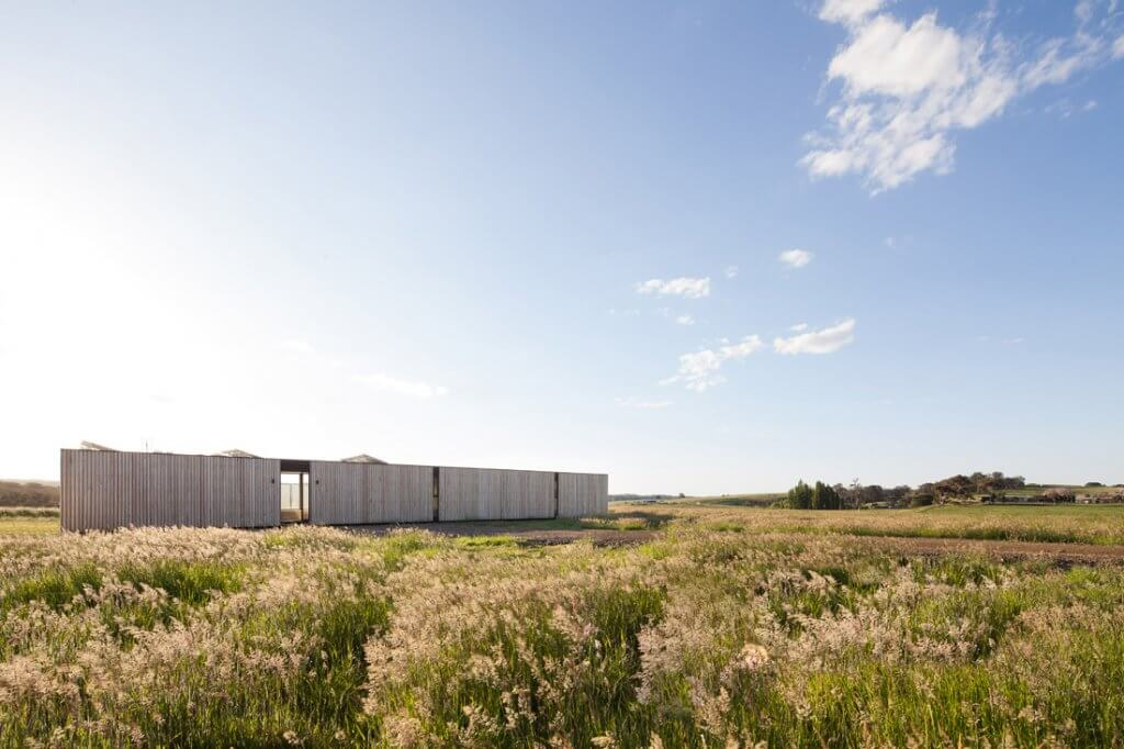 Timber modular home surrounded by a grass field