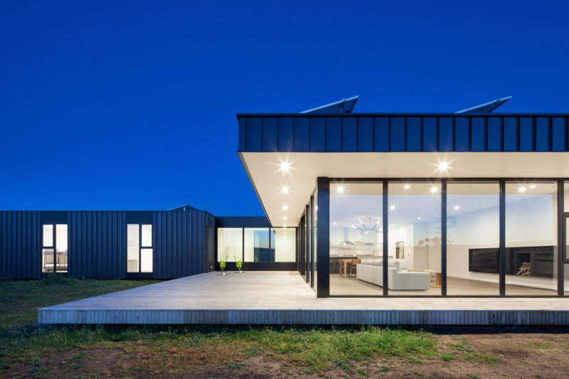 Modern modular home at dusk with lights on