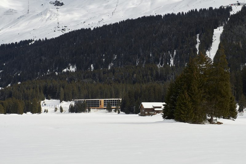 Hotel Revier surrounded by snow and fir trees.