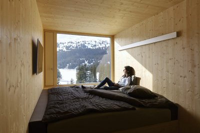 A Hotel Revier guest sitting on a bed and looking out the window at the mountainous view beyond.